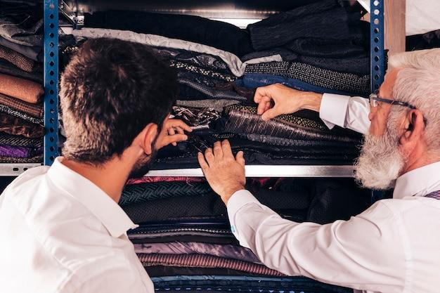 Close-up, de, homem, e, macho, alfaiate sênior, selecionar, a, tecido, em, a, prateleira Foto gratuita