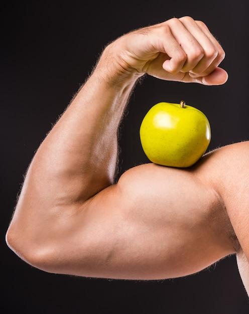 Close-up de homem musculoso mostrando seu bíceps perfeito. Foto Premium