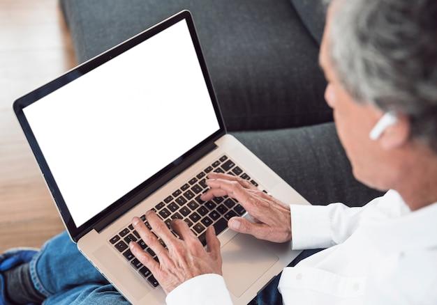 Close-up, de, homem sênior, usando computador portátil, com, tela branca Foto gratuita