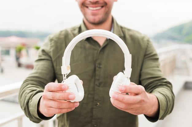 Close-up, de, homem sorridente, mostrando, branca, headphone Foto gratuita