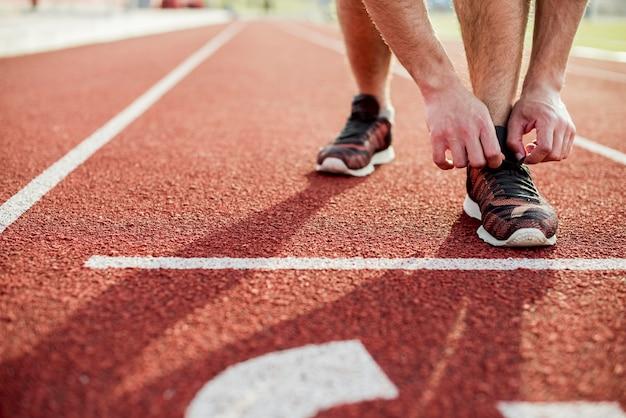 Close-up de jovem amarrando o sapato esportivo na pista de corrida vermelha Foto gratuita