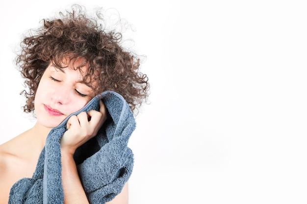 Close-up de jovem enxuga o rosto com uma toalha isolada no fundo branco Foto gratuita