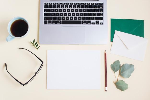 Close-up de laptop com envelope; papel; lápis; óculos; xícara de chá e óculos em pano de fundo colorido Foto gratuita
