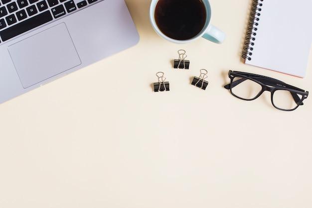 Close-up de laptop; xícara de chá; clipe de papel; óculos e bloco de notas em espiral no pano de fundo bege Foto gratuita