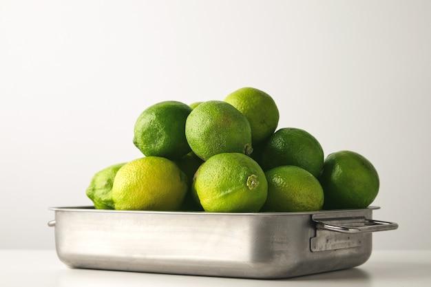 Close up de limão fresco em uma panela de aço isolada na mesa branca. Foto gratuita