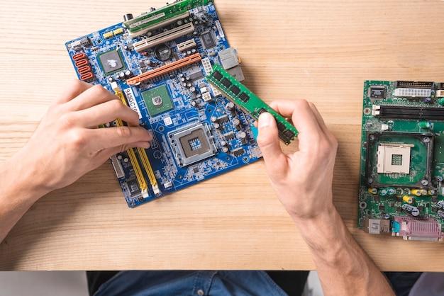 Close-up, de, macho, aquilo, técnico, reparar, mainboard, computador eletrônico, ligado, tabela madeira Foto gratuita