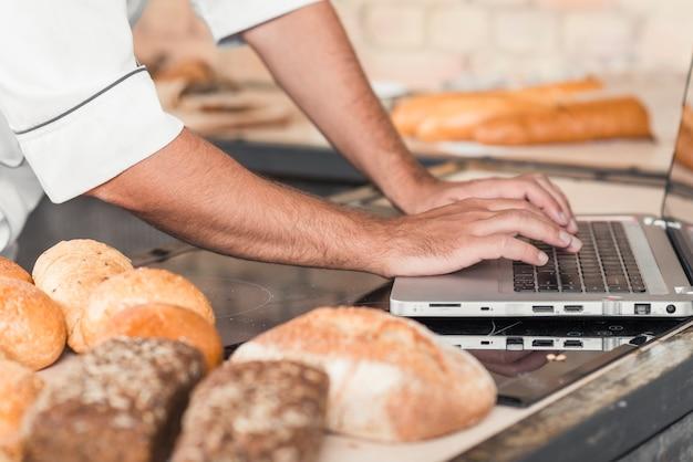 Close-up, de, macho, baker's, mão, usando computador portátil, ligado, cozinha, worktop, com, pães Foto gratuita