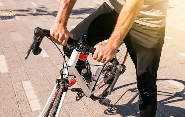 Close-up, de, macho, ciclista, montando, seu, bicicleta Foto gratuita