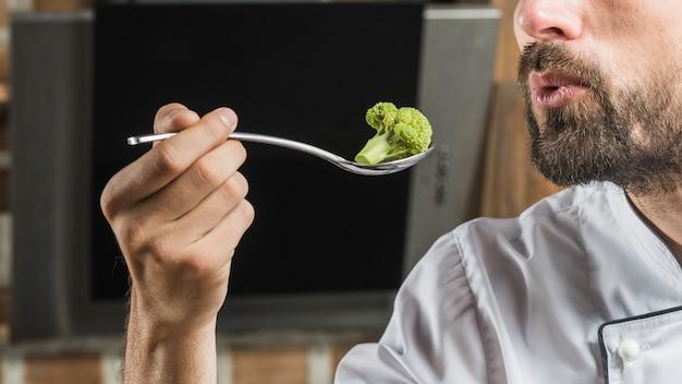 Close-up, de, macho, cozinheiro, segurando, brócolos, em, colher, com, seu, mão Foto gratuita