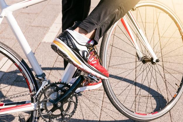 Close-up, de, macho, desgastar, calças brim, e, desgastar, sapatas do esporte, passeios, bicicleta, parque Foto gratuita