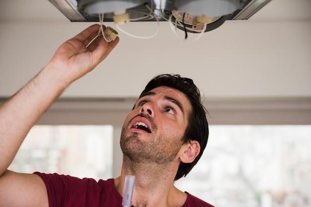 Close-up, de, macho, eletricista, instalar, suporte, de, luz teto Foto gratuita