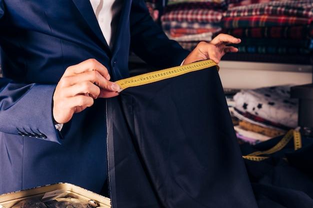 Close-up, de, macho, moda, desenhista, mão, levando, medida, de, azul, tecido, com, amarela, medindo fita Foto gratuita