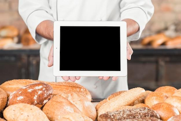 Close-up, de, macho, padeiro, mostrando, em branco, tablete digital, sobre, a, pão assado Foto gratuita