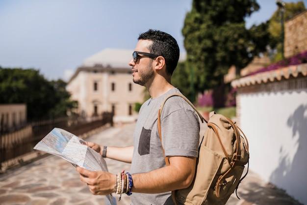 Close-up, de, macho, turista, segurando, mapa, em, seu, mão Foto gratuita