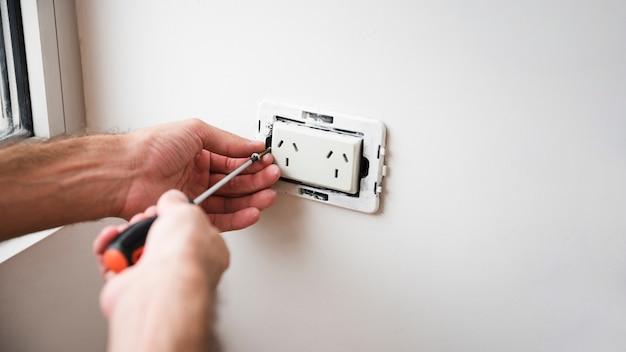 Close-up, de, mão, afixando, tomada plugue, branco, parede Foto gratuita
