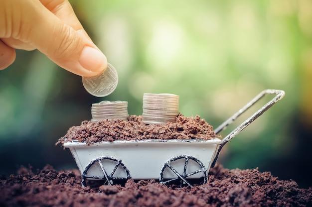 Close-up de mão colocando moedas na pilha de moedas está crescendo no carrinho de mão para investimento empresarial ou conceito de poupança Foto Premium