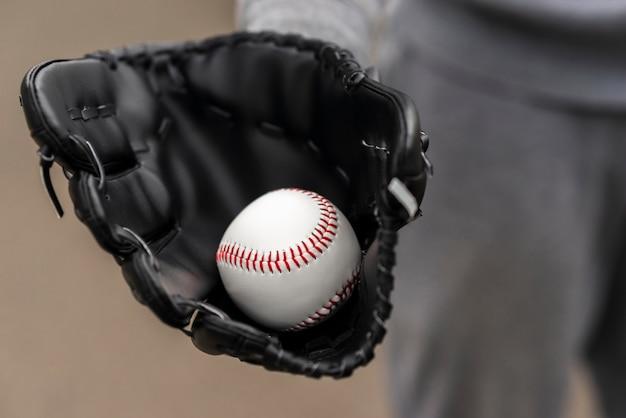 Close-up de mão com luva segurando beisebol Foto gratuita