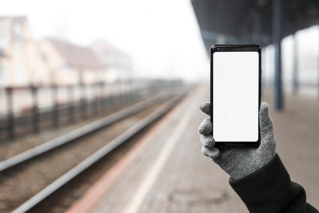 Close-up, de, mão, desgastar, luvas, segurando, telefone móvel, mostrando, em branco, tela branca, em, estação de comboios Foto gratuita