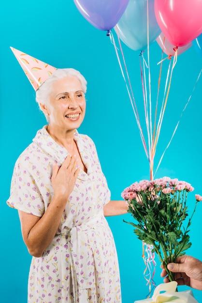 Close-up, de, mão homem, dar, flores, e, presente aniversário, para, mulher sênior Foto gratuita