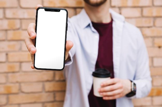 Close-up, de, mão homem, mostrando, smartphone, com, em branco, tela branca Foto gratuita