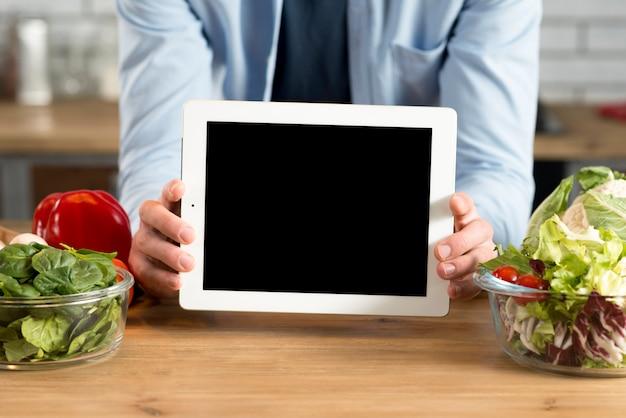 Close-up, de, mão homem, mostrando, tablete digital, com, tela em branco, em, cozinha Foto gratuita