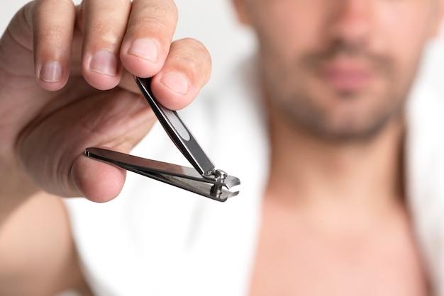 Close-up, de, mão homem, segurando, cortador unha Foto gratuita