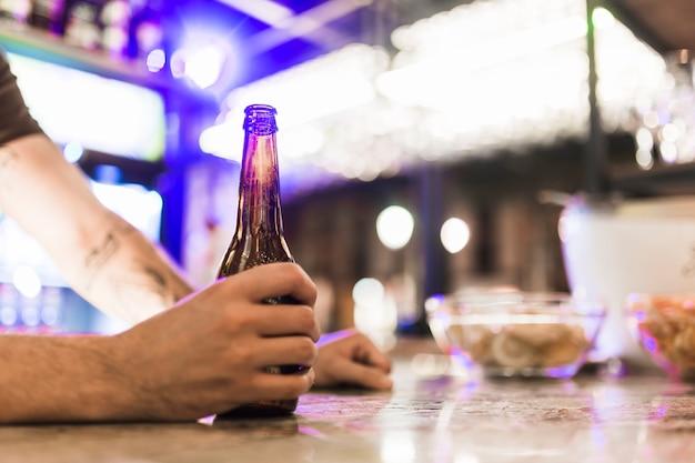 Close-up, de, mão homem, segurando, garrafa cerveja, em, a, barzinhos Foto gratuita