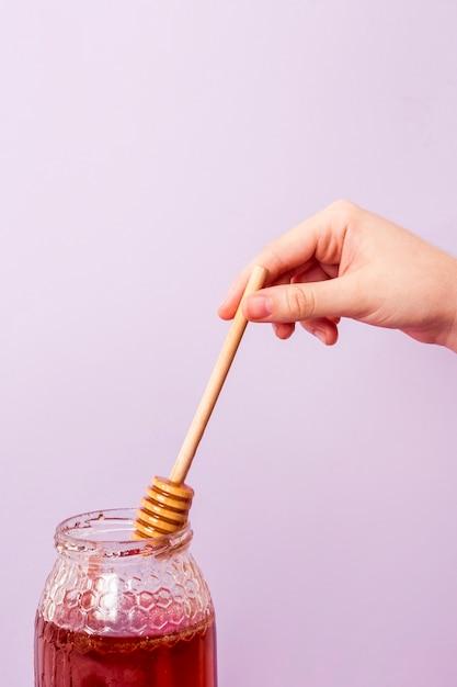Close-up, de, mão humana, colheita, mel, de, jarro Foto gratuita