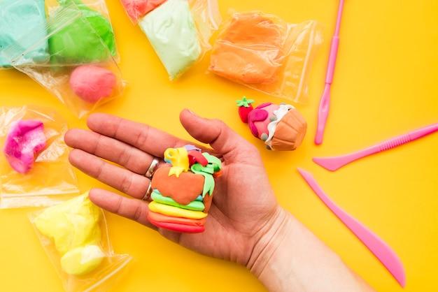 Close-up, de, mão humana, mostrando, decorativo, argila, ligado, experiência amarela Foto gratuita