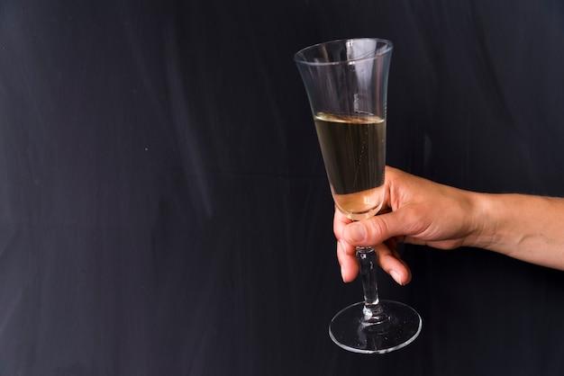 Close-up, de, mão humana, segurando, bebida alcoólica, vidro, ligado, pretas, fundo Foto gratuita