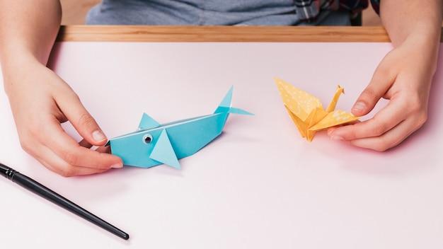 Close-up, de, mão humana, segurando, origami, peixe, e, pássaro Foto gratuita
