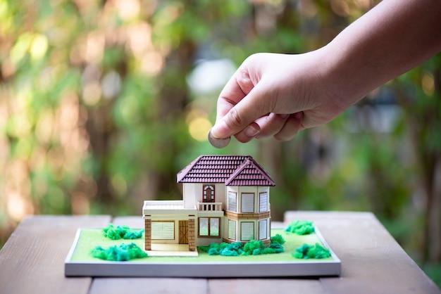 Close-up de mão inserir moedas na casa modelo na mesa de madeira Foto Premium