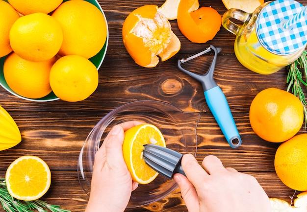 Close-up, de, mão mulher, fazer, suco fresco laranja, ligado, tabela madeira Foto gratuita