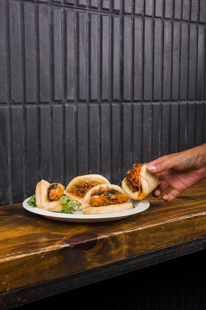 Close-up, de, mão mulher, guiando, gua, bao, ligado, prato branco, sobre, a, tabela madeira Foto gratuita