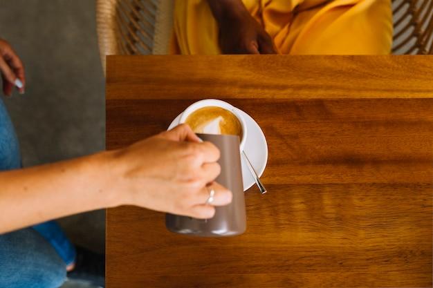 Close-up, de, mão mulher, leite derramando, em, a, copo, ligado, tabela Foto gratuita