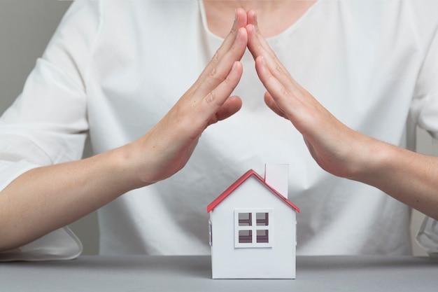 Close-up, de, mão mulher, protegendo, casa, modelo, ligado, cinzento, superfície Foto gratuita