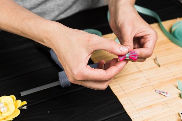 Close-up, de, mão mulher, segurando, grampo cabelo rosa Foto gratuita