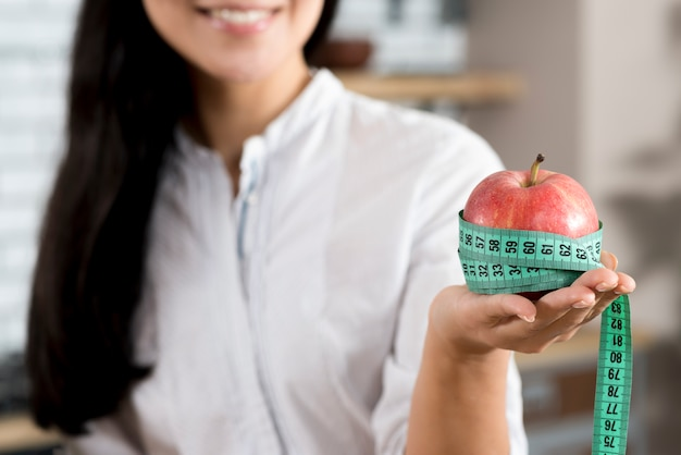 Close-up, de, mão mulher, segurando, maçã vermelha, com, medida verde, fita Foto gratuita