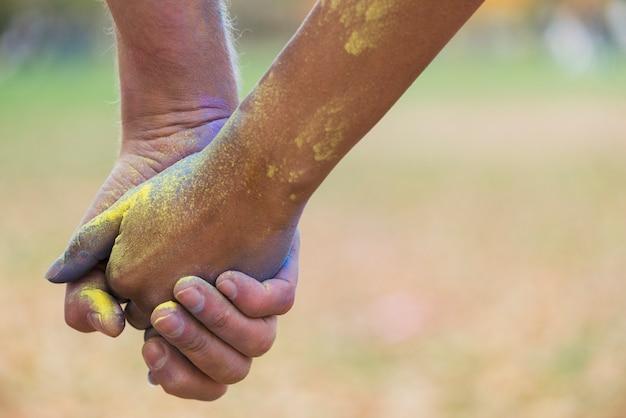 Close-up de mãos dadas enquanto coberto de tinta Foto gratuita