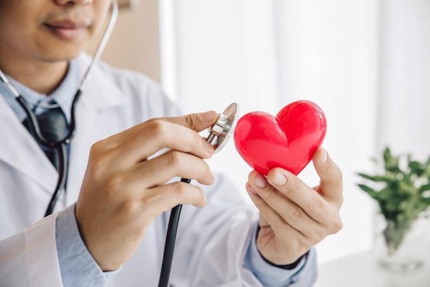 Close-up de mãos de médico com coração vermelho com estetoscópio Foto Premium