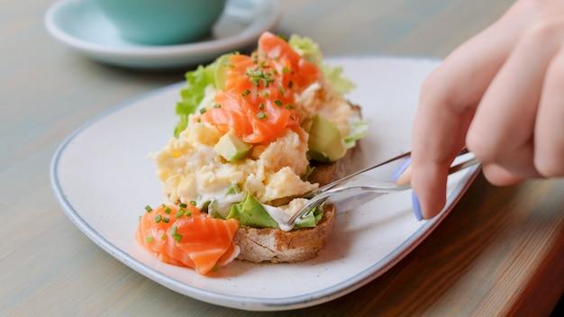 Close up de mãos femininas cortando torradas de abacate com salmão e ovo enquanto tomando café da manhã Foto Premium