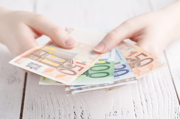 Close-up de mãos femininas segurando algumas notas de euro Foto Premium