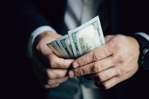 Close-up de mãos masculinas contando notas de dólar Foto Premium