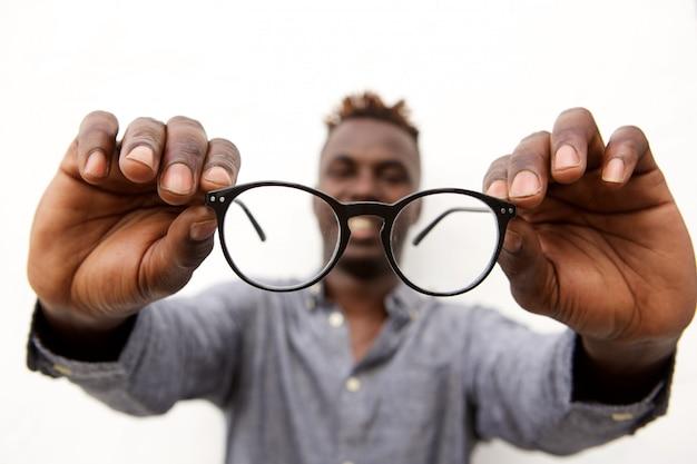 Close up de mãos masculinas segurando um par de óculos Foto Premium