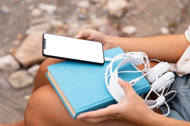 Close-up de mãos segurando um telefone e fones de ouvido Foto gratuita