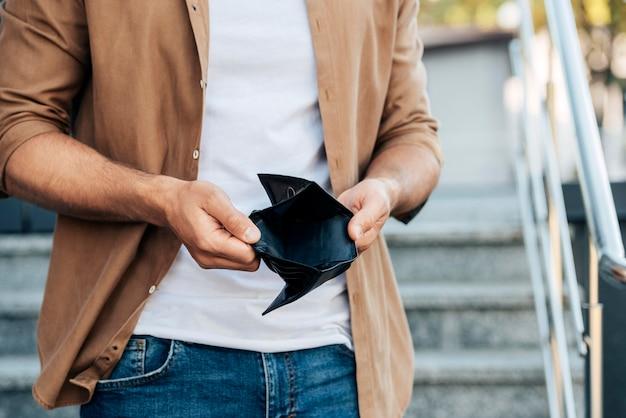 Close-up de mãos segurando uma carteira vazia Foto gratuita