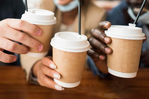 Close-up de mãos segurando xícaras de café Foto gratuita