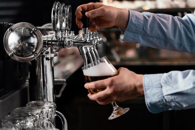 Close-up de mãos servindo cerveja no copo Foto gratuita