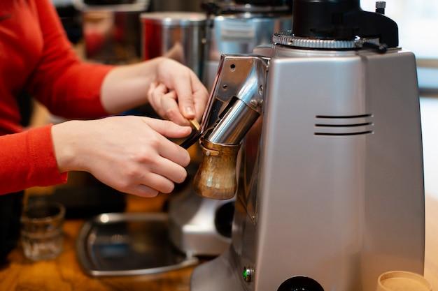 Close-up de mãos trabalhando na máquina de café Foto gratuita
