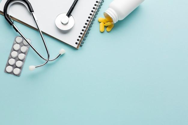 Close-up de medicina embalada em blister; estetoscópio; bloco de notas em espiral acima de fundo azul Foto gratuita